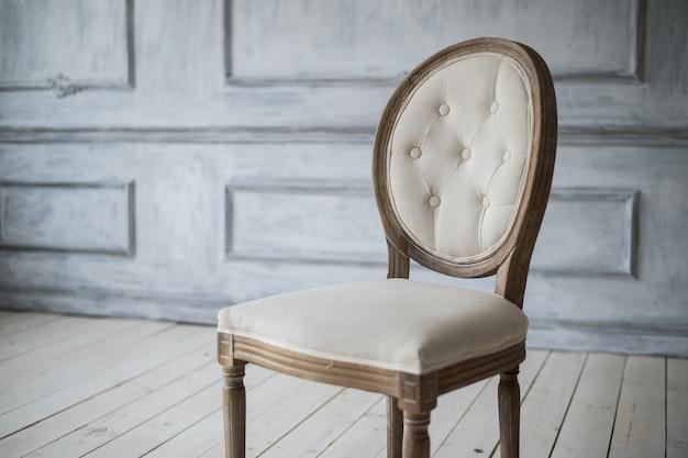 Chaise vintage blanche debout devant un mur clair avec moulures sur parquet en bois.