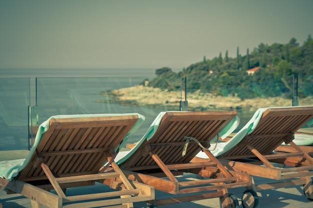Chaises au bord de la piscine de l'hôtel avec vue sur la mer. tir horizontal de style vintage