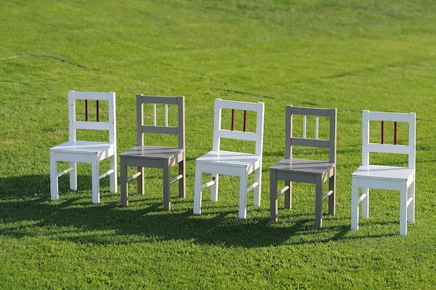 Chaises en bois dans un champ d'herbe verte