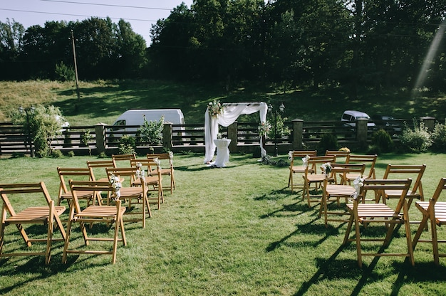 Des chaises brunes se tiennent devant un autel weding sur une pelouse d'herbe