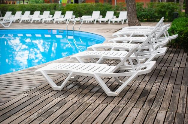 Chaises longues au bord de la piscine au centre de loisirs