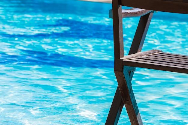 Chaises longues, chaises piscine de luxe eau bleue pour la détente sur les vacances de voyage d'été sur la plage