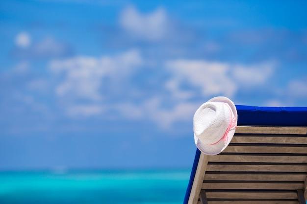 Chaises longues avec chapeau sur la plage blanche tropicale