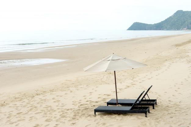 Chaises longues avec parasols blancs