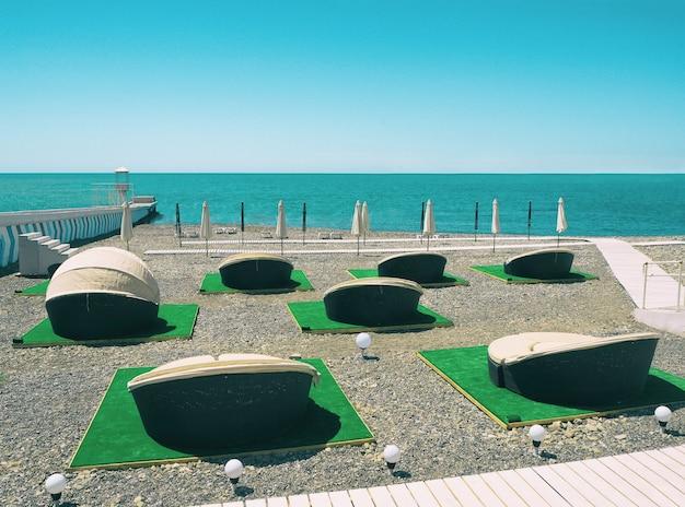 Chaises longues en plein air ou chaises longues de patio sur la plage au fond bleu de la mer et du ciel