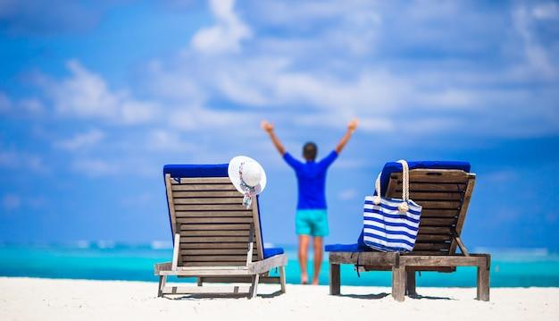 Chaises longues avec sac et chapeau sur la plage blanche tropicale