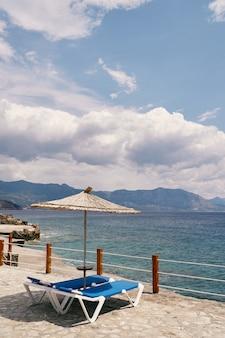Des chaises longues se tiennent sous un parasol derrière une clôture surplombant la mer