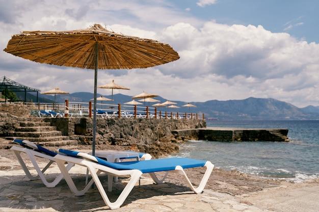 Des chaises longues se tiennent sous un parasol près de l'eau