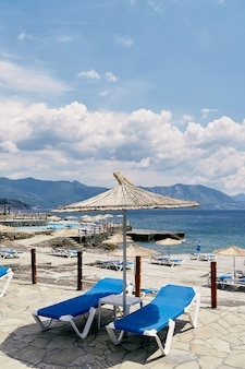 Chaises longues sous un parasol en paille sur des pavés près de la mer