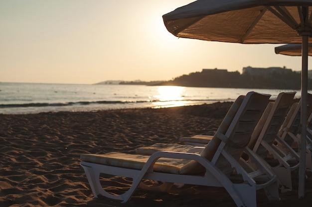 Chaises longues et transats gratuits sur la plage. photo douce et lumineuse