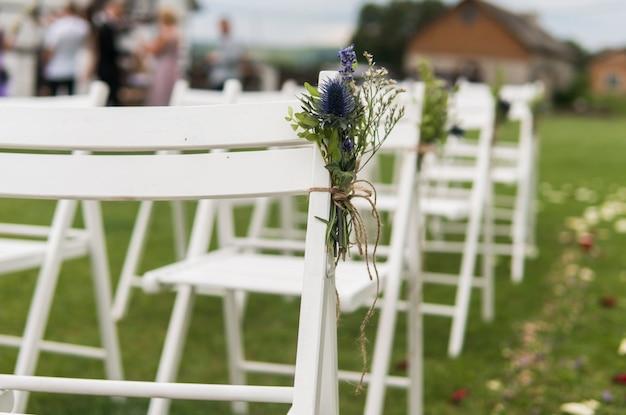 Chaises de mariage blanches décorées de fleurs fraîches sur une herbe verte. chaises en bois vides pour les clients sur la pelouse verte dans le jardin préparé pour la cérémonie de mariage.