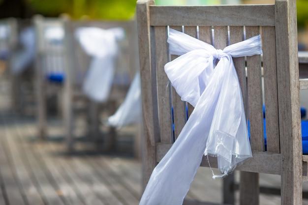 Chaises de mariage décorées d'arcs blancs au café en plein air