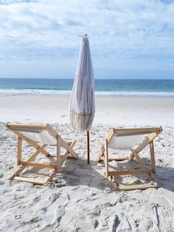 Chaises avec parasol sur la plage de sable blanc près du concept de vacances d'été de la mer