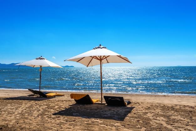 Chaises et parasol sur une plage tropicale.