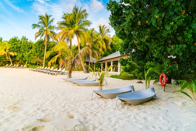 Chaises de plage dans les îles maldives au lever du soleil.