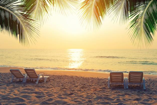 Des chaises de plage avec des feuilles de noix de coco sur la plage tropicale au coucher du soleil. concept de voyage d'été.