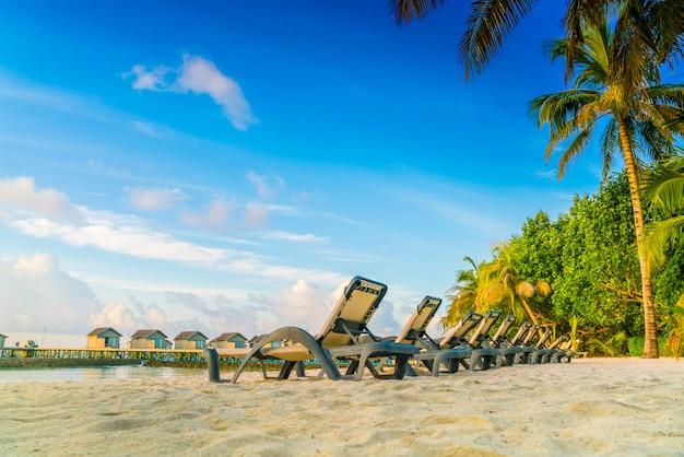 Chaises de plage sur l'île des maldives avec villas sur l'eau au lever du soleil.