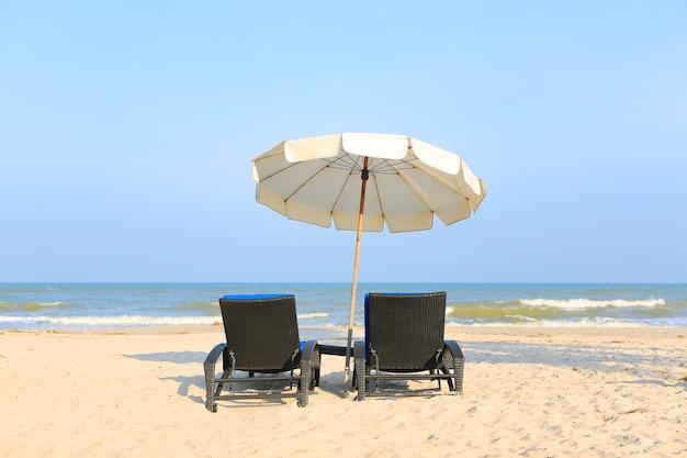 Chaises de plage sur la plage de sable avec parasol blanc sur ciel bleu nuageux et soleil