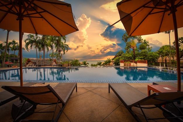 Chaises de plage près de la piscine au coucher du soleil