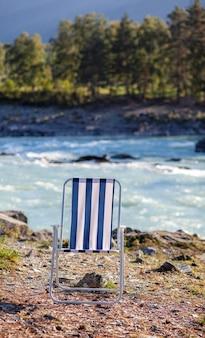 Chaises pliantes au bord d'une rivière de montagne par une belle journée chaude. un endroit calme et tranquille pour se détendre et réfléchir. l'équipement et le repos d'un touriste.