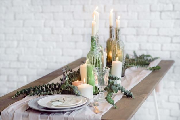 Chaises et table pour les invités, décorées de bougies, servies avec couverts et vaisselle et recouvertes d'une nappe.
