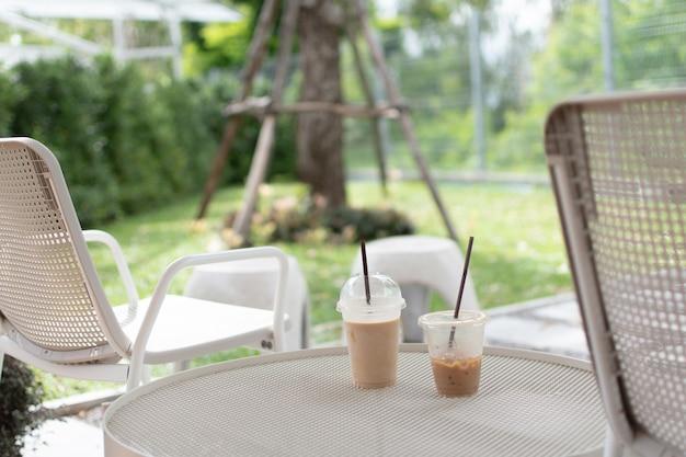 Des chaises et des tables blanches sont placées dans le jardin. et deux verres ont été placés sur la table.