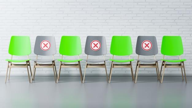 Les chaises vertes et grises sont dans une pièce vide contre le mur. le concept de distance sociale.