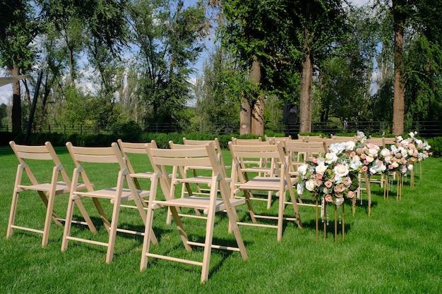 Chaises vides en bois blancs dans une rangée et bouquets de fleurs sur l'herbe verte. décorations de mariage