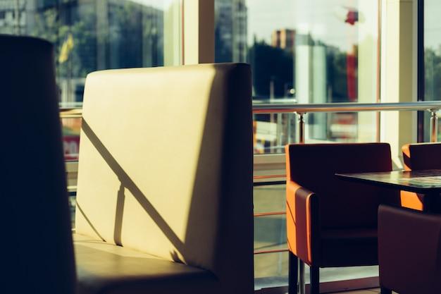Chaises vides dans un café avec une fenêtre panoramique