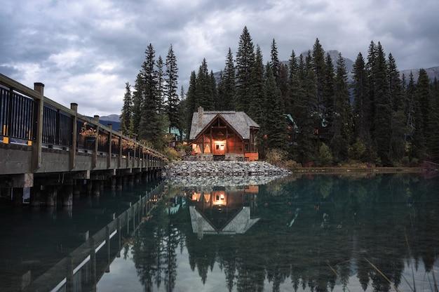 Chalet en bois brillant avec forêt de pins et réflexion de pont