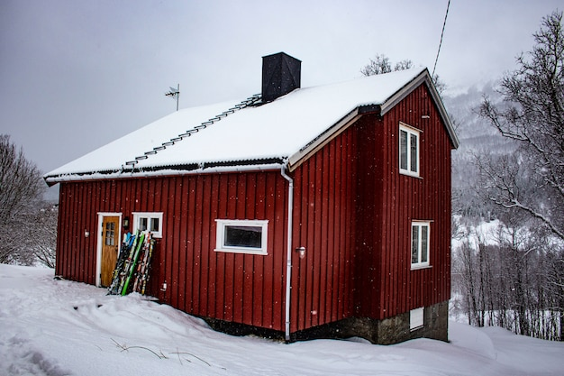 Chalet norvégien rouge en hiver, avec ski à l'avant, norway house