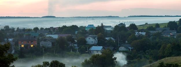 Chalets résidentiels parmi les arbres verts recouverts de brouillard bleu
