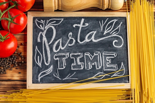 Chalk board sign pasta time sur une table en bois avec des spaghettis crus, des tomates fraîches et du poivre noir.