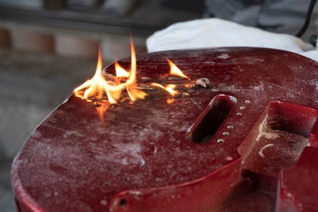 Chalumeau flamme brûlant sur une guitare rouge fixe.