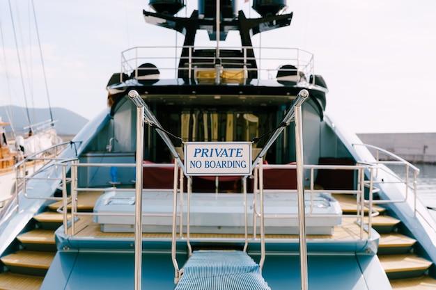 Chalut de poupe d'un beau yacht à moteur blanc avec une inscription d'échelle en bois privé pas d'embarquement