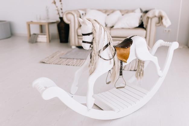 Chambre bébé dans un style scandinave blanc avec cheval à bascule