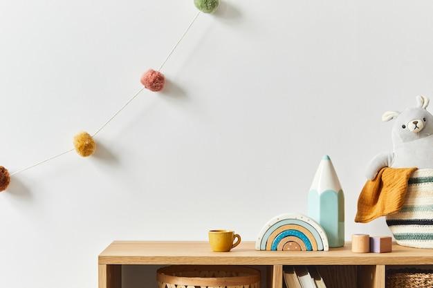 Chambre bébé nouveau-né scandinave élégante avec jouets, animaux en peluche, poupées et accessoires pour enfants. décoration cosy et boules de coton suspendues au mur blanc. espace de copie.