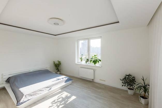 Chambre blanche avec éléments en brique, balcon, lit double, bureau