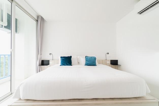 Une chambre blanche avec un lit en bois, des draps et un oreiller avec une cape blanche.