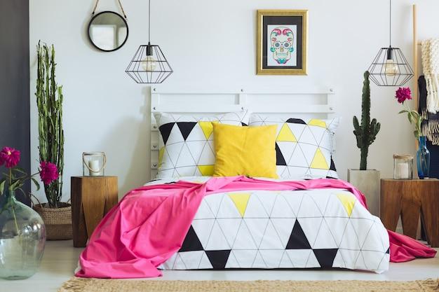 Chambre blanche unique avec des oreillers colorés, des draps géométriques et des cactus