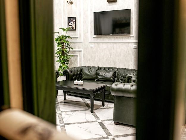 Une chambre avec canapé en cuir vert