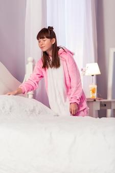 Chambre confortable. kind brunette portant un pyjama doux et regardant un oreiller blanc