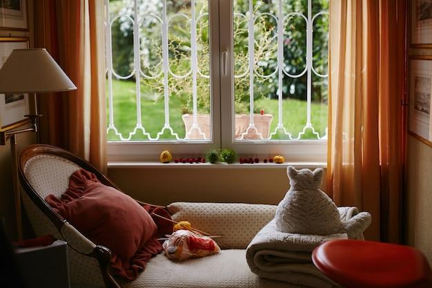 Chambre confortable pêche et beige avec canapé vintage blanc chat en peluche et lampe, intérieur mignon