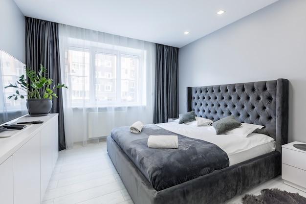 Chambre à coucher moderne avec grand lit en gris de couleurs sombres