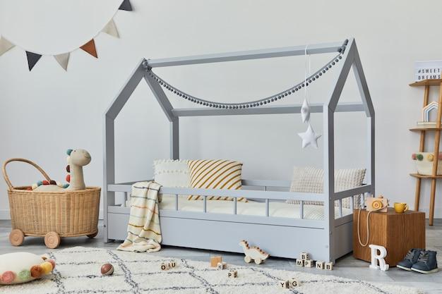 Chambre d'enfant scandinave élégante avec des jouets de lit créatifs et un modèle de décorations textiles suspendues