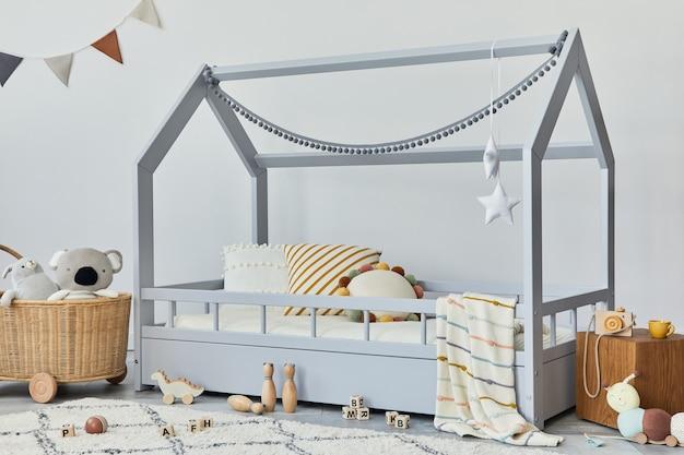 Chambre d'enfant scandinave élégante avec lit en bois créatif, cube en bois, lampe, étagère en bois, peluches et jouets en bois et décorations textiles suspendues. murs gris. modèle.