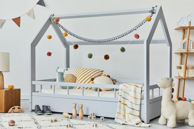 Chambre d'enfant scandinave élégante avec lit en bois créatif, oreillers, cube en bois, lampe, étagère en bois, peluches et jouets en bois et décorations textiles suspendues. murs gris, moquette au sol. modèle.