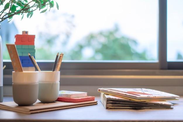 Chambre d'enfants avec des crayons et des livres sur la table près de la fenêtre.