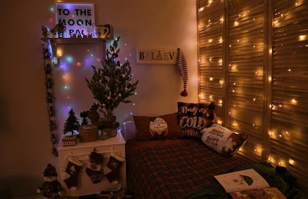 Chambre d'enfants décorée pour noël et le nouvel an, avec un lit et des lumières, dans des couleurs classiques rouge-vert