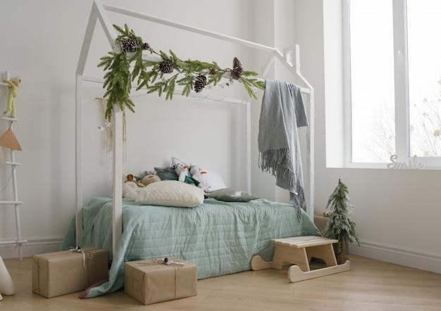 Chambre d'enfants avec lit en forme de maison décorée pour noël avec des coffrets cadeaux et un traîneau en bois